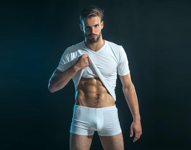 L'uomo in boxer mostra i muscoli addominali. uomo sexy muscoloso in maglietta bianca che mostra pres.