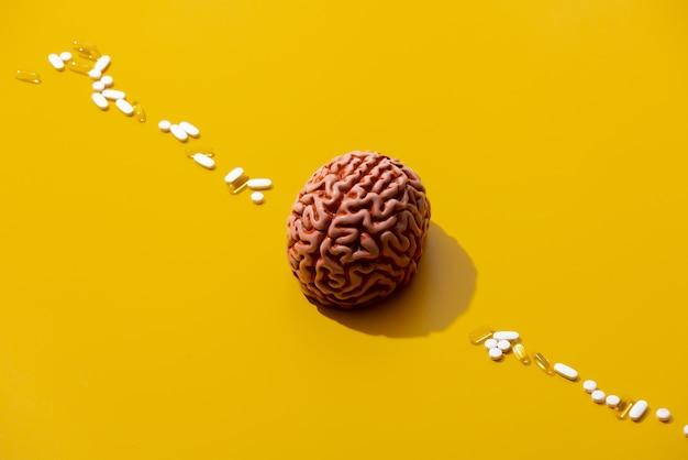Cervello dell'uomo e pillole intorno sulla superficie gialla