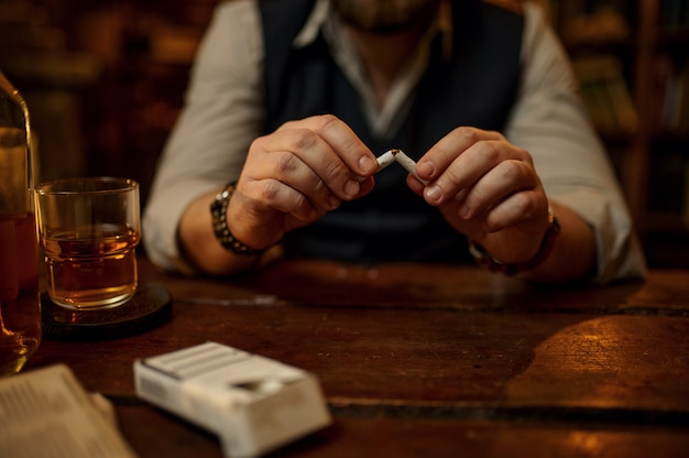L'uomo rompe una sigaretta, cattiva abitudine e dipendenza, bevanda alcolica sul tavolo, interno dell'ufficio vintage. cultura del fumo di tabacco, sapore specifico