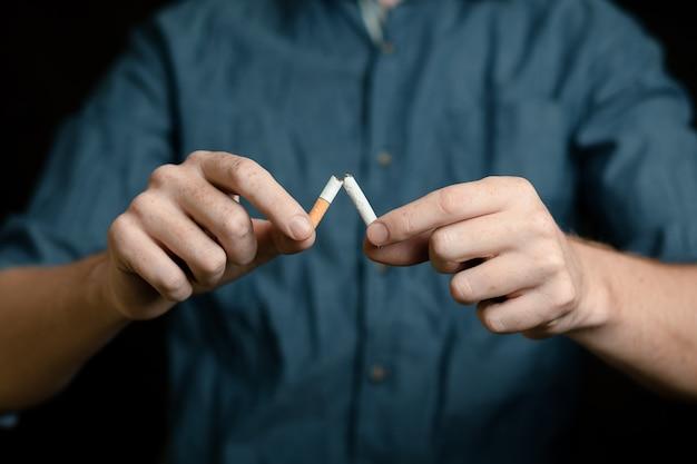 L'uomo rompe una sigaretta. sulla superficie nera
