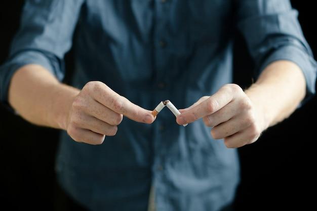 L'uomo rompe una sigaretta. nozione di divieto di fumo