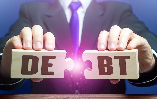 L'uomo rompe i puzzle con la parola debiti ristrutturazione del debito distress finanziario rifinanziamento degli allenamenti di prestito