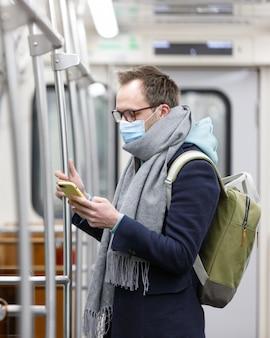 Uomo che respira attraverso una mascherina medica a causa del pericolo di contrarre il virus dell'influenza, il coronavirus