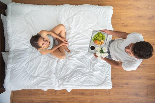 L'uomo che porta la colazione per una donna sul letto. vista dall'alto
