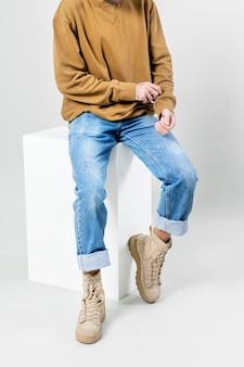 Uomo in maglione marrone e jeans blu