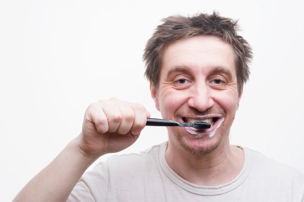 Un uomo si lava i denti dopo aver mangiato su uno sfondo bianco