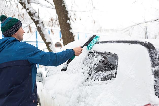 Un uomo spazza la neve da un'auto dopo una nevicata.