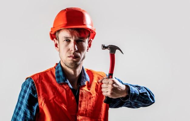 Costruttore dell'uomo isolato sulla parete bianca. martello a martello. costruttore in casco, martello, tuttofare, costruttori in elmetto protettivo. lavoratore uomo con barba, casco da costruzione, elmetto.