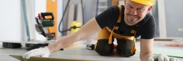 Uomo costruttore in casco giallo sdraiato tavole laminate sul pavimento