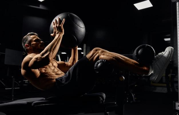 Uomo che costruisce i muscoli del core con la palla.