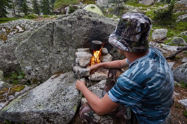 L'uomo ha costruito un falò nel bosco in natura. sopravvivere in montagna nella foresta, cucinando in una pentola