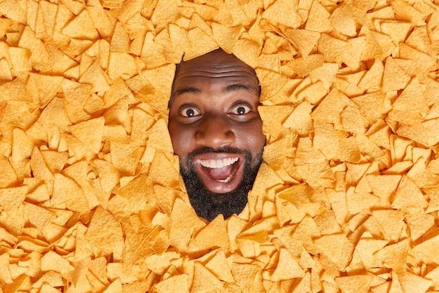 L'uomo sepolto nelle patatine guarda con un'espressione felice ed eccitata tiene la bocca aperta preferisce il cibo dannoso si diverte a mangiare uno spuntino gustoso