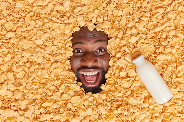 L'uomo sepolto in un mucchio di fiocchi di mais con una bottiglia di latte vicino tiene la bocca spalancata ha un umore felice esprime emozioni positive