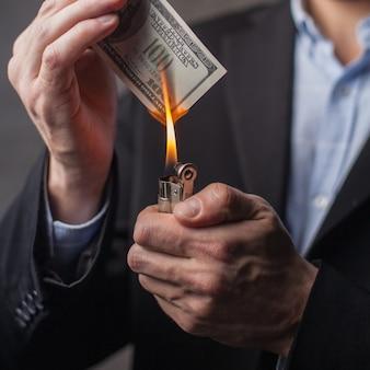 Uomo che brucia una banconota da cento dollari. avvicinamento