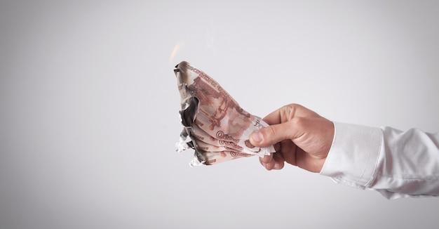 Banconota bruciante dei rubli russi dell'uomo.