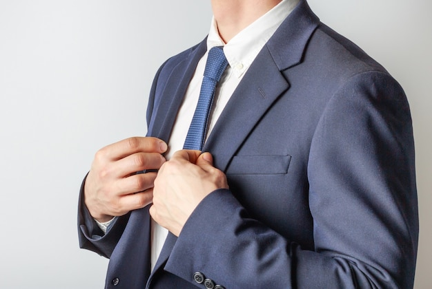 Un uomo in giacca e cravatta si aggiusta la giacca