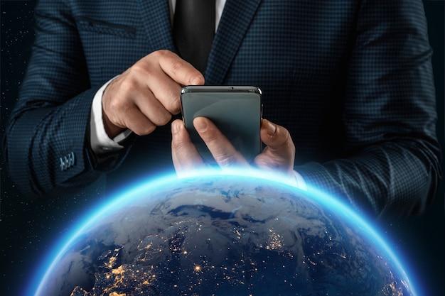 Un uomo in giacca e cravatta, un uomo d'affari tiene uno smartphone davanti al globo