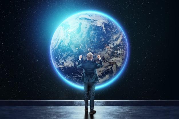 Un uomo in giacca e cravatta, un uomo d'affari si erge sullo sfondo del globo