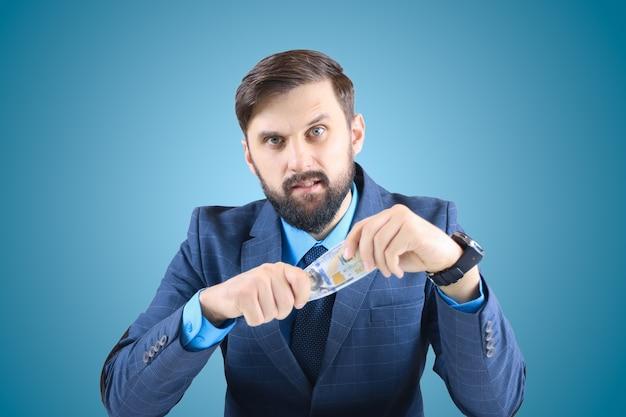 Un uomo in giacca e cravatta tiene in mano banconote da un dollaro e guarda dritto, un uomo d'affari con banconote in mano Foto Premium