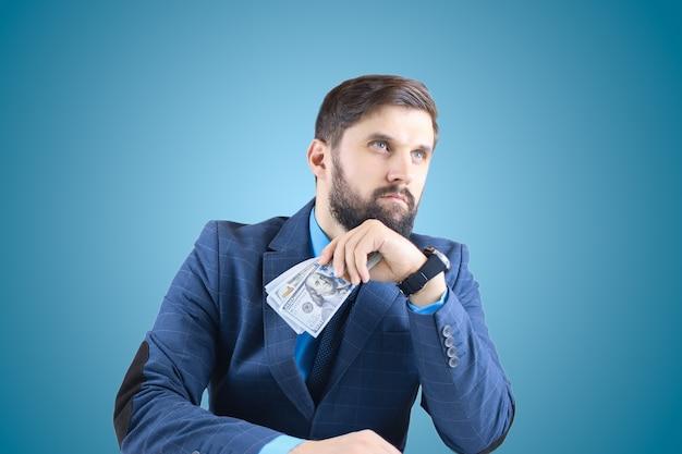 Un uomo in giacca e cravatta tiene in mano banconote da un dollaro e guarda dritto, un uomo d'affari con banconote in mano
