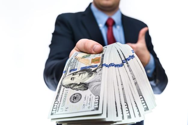 L'uomo in giacca e cravatta tiene i tagli da cento dollari