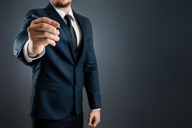 Un uomo in giacca e cravatta tende la mano con una penna a sfera, scrive nell'aria.