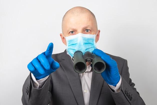 L'uomo in giacca e cravatta in una maschera medica e guanti protettivi guarda attraverso il binocolo. obiettivi in un'azienda di successo con problemi di quarantena nell'epidemia di coronavirus.