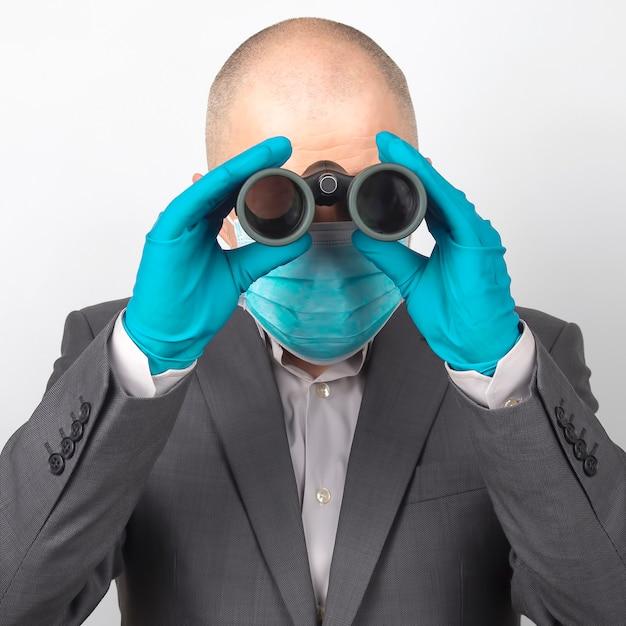Uomo in giacca e cravatta in una maschera medica e guanti protettivi
