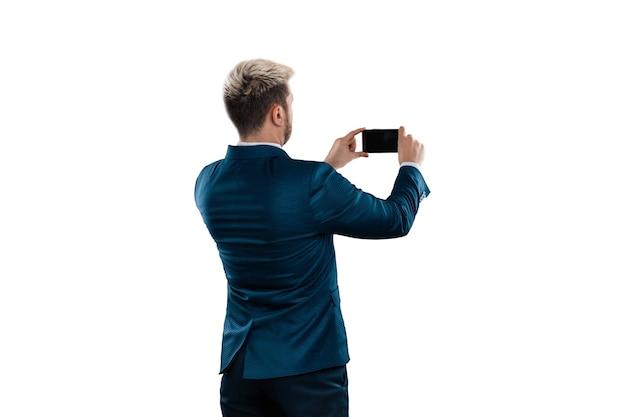 Un uomo in giacca e cravatta fotografa qualcosa