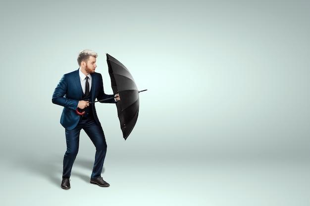 Un uomo in giacca e cravatta sta con un ombrello in mano su uno sfondo chiaro