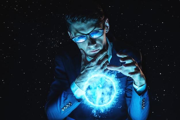 L'uomo d'affari dell'uomo che tiene le mani sopra una sfera d'ardore blu del plasma. previsione magica e lungimiranza nel mondo degli affari e della finanza
