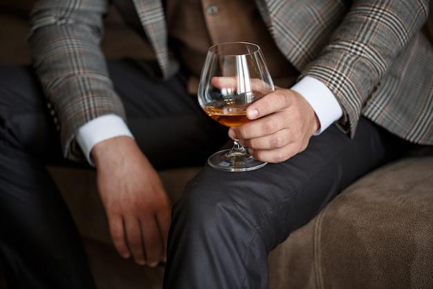 Un uomo d'affari tiene in mano un bicchiere con dell'alcol. vestito con una giacca e una camicia. riposo dopo una giornata di lavoro