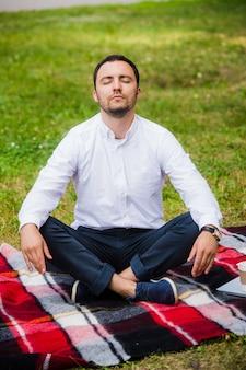 Uomo d'affari dell'uomo meditando all'aperto nella posa del loto