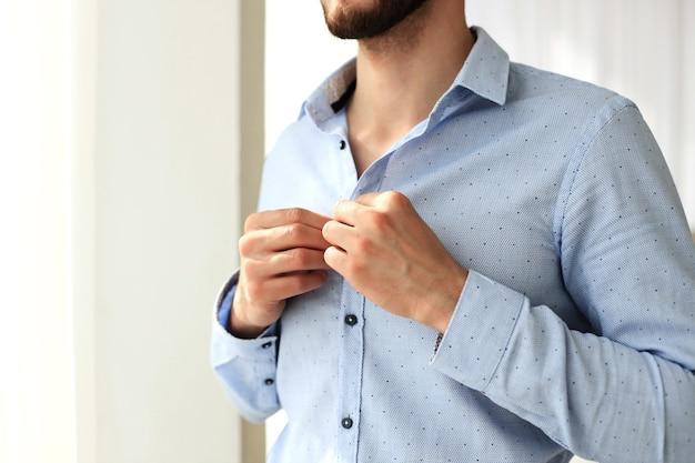 L'uomo abbottona le maniche sulla camicia di lino blu in camera da letto leggermente inclinata.