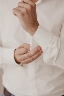 L'uomo abbottona i bottoni della camicia