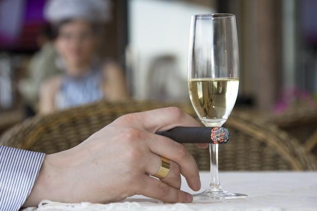 Uomo al bar che beve vino e fuma un sigaro
