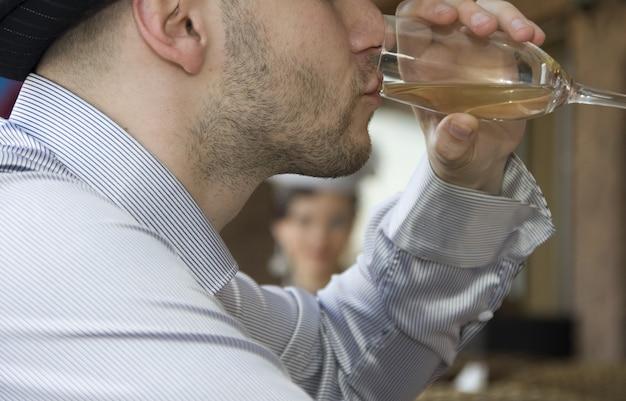 Uomo al bar che beve vino