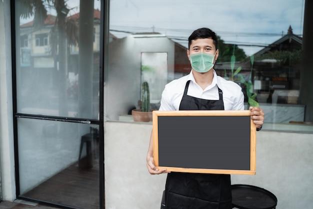 Bordo in bianco della stretta del lavoratore del caffè dell'uomo