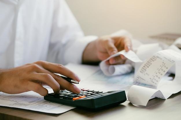 L'uomo calcola le bollette domestiche a casa l'uomo che utilizza una calcolatrice controlla il saldo e i costi in ufficio
