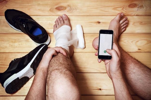 L'uomo chiama i servizi di emergenza seduto sul pavimento di legno. lesioni sportive. vista dall'alto