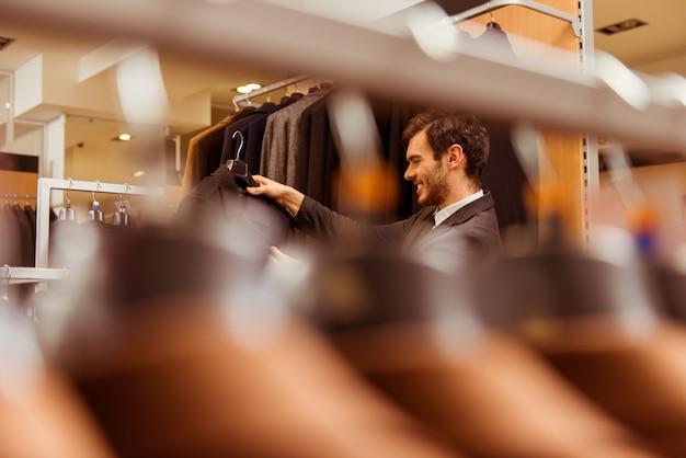 Un uomo è venuto in un negozio di abbigliamento per selezionare un abito.