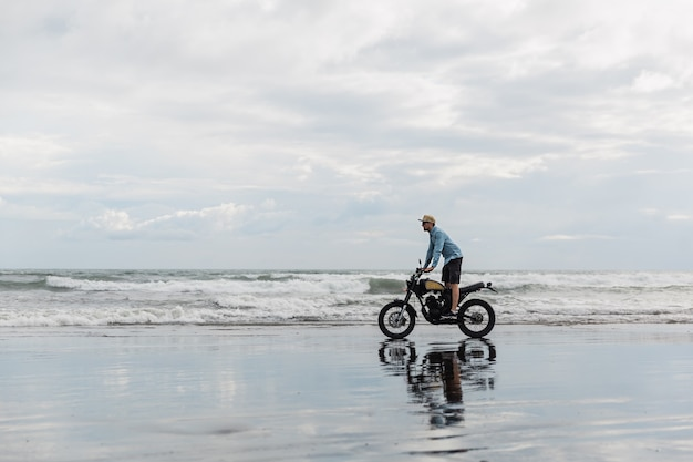 Uomo in berretto in sella moto sulla spiaggia. moto cross dirtbiker sulla spiaggia al tramonto a bali. giovane maschio hipster che gode della libertà e dello stile di vita attivo, divertendosi in un tour di motociclisti.