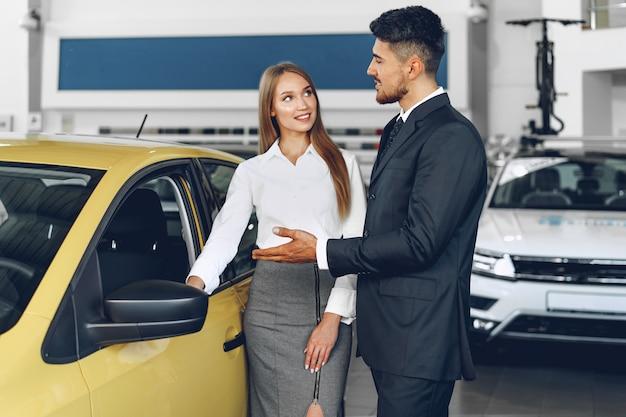 Rivenditore di auto uomo che mostra a un acquirente donna una nuova auto