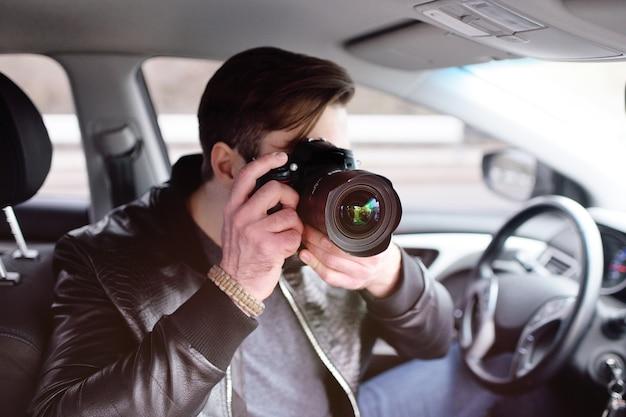 L'uomo in macchina esamina le foto sulla fotocamera. spia, paparazzi, giornalista, fotografo.