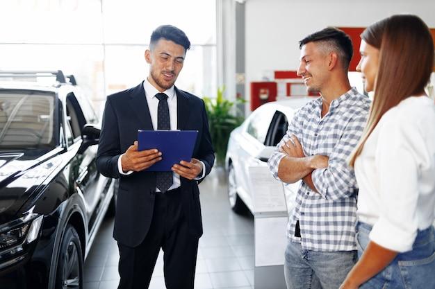 Venditore di auto uomo che racconta alla coppia le caratteristiche della nuova vettura