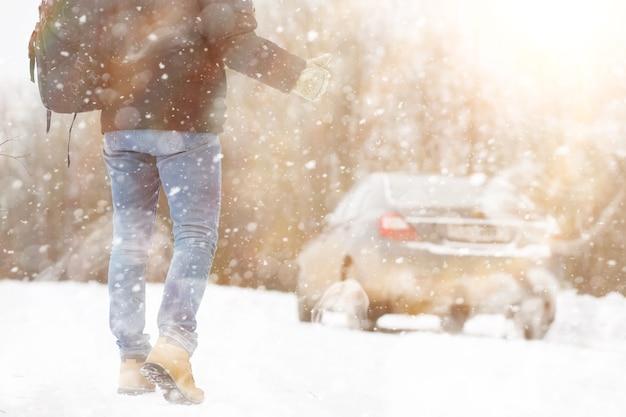 Uomo e macchina. passeggiata invernale e riparazione auto.