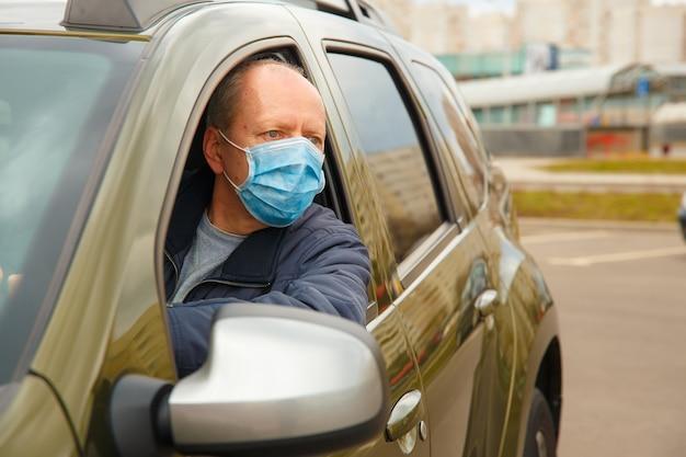 Un uomo in macchina con maschera protettiva contro la diffusione del coronavirus
