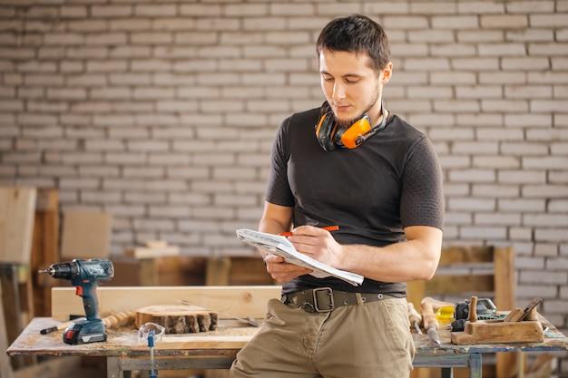 Il carpentiere dell'uomo nel suo studio domestico disegna gli schizzi a matita in taccuino