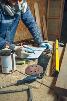 L'uomo falegname nel suo studio di casa lavora con il legno e disegna schizzi a matita in un taccuino