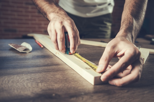 L'uomo falegname misura la tavola di legno
